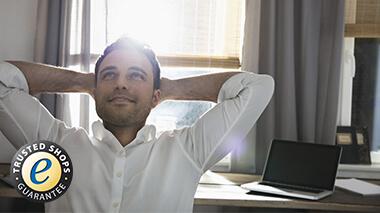Junger Mann mit Laptop beim Online-Einkauf